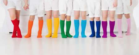 Kids wearing colorful rainbow socks. Children footwear collection. Variety of knitted knee high socks and tights. Child clothing and apparel. Kid fashion. Legs and feet of little boy and girl group. Stock Photo