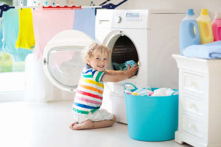Child in a laundry room with washing machine or tumble dryer. Kid helping with family chores. Modern household devices and washing detergent in white sunny home. Clean washed clothes on drying rack. Archivio Fotografico