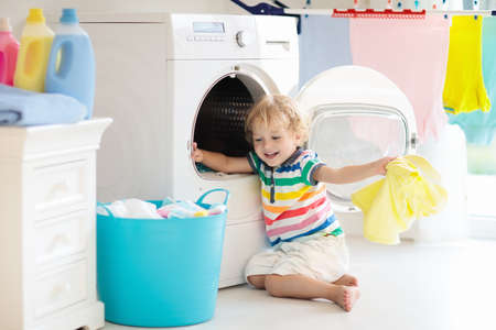 Child in a laundry room with washing machine or tumble dryer. Kid helping with family chores. Modern household devices and washing detergent in white sunny home. Clean washed clothes on drying rack. 版權商用圖片