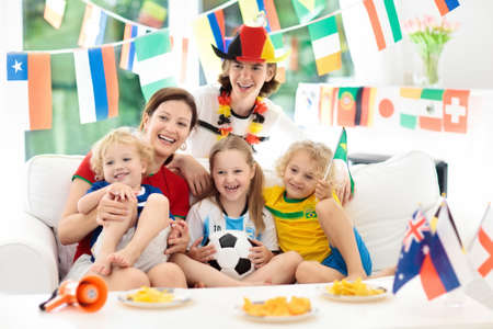 Family with children watching football game on television. Group of young adults and kids in national tricot watch soccer match on tv. Fans cheering and supporting country team at championship.
