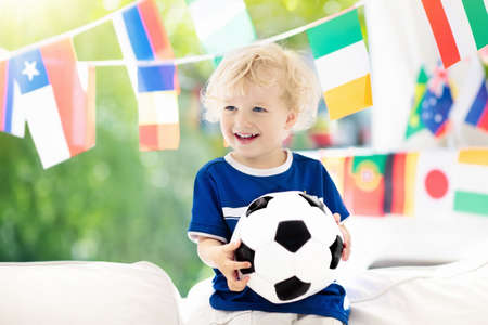 Child watching football game on tv. Little boy in France tricot watching soccer game during championship. Kid fan cheering and supporting national team. Young football player with ball before match.