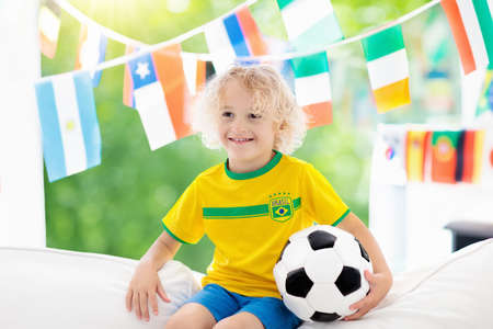 Child watching football game on tv. Little boy in Brazil tricot watching soccer game during championship. Kid fan cheering and supporting national team. Young football player with ball before match. Banco de Imagens