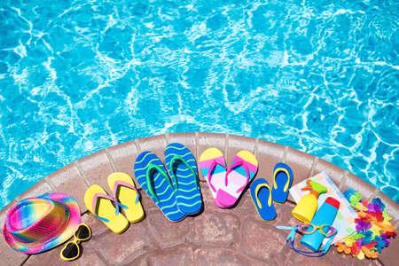 Schwimmbadzubehör flach legen. Draufsicht auf Strandgegenstände auf Pooldeck. Flip Flops, Bikini und Hut, Sonnenbrille. Wasserspielzeug. Sommerferien im tropischen Ferienort. Speicherplatz kopieren. Bunte Strandkleidung.