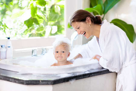Little child taking a bubble bath in a beautiful bathroom with a big garden view window. Mother washing baby. Kids hygiene. Shampoo, hair treatment and soap foam for children. Mom bathing kid in large tub. Stock Photo