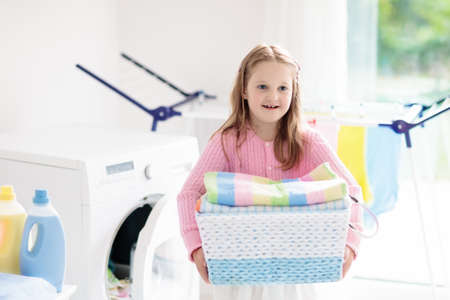 Child in laundry room with washing machine or tumble dryer. Kid helping with family chores. Modern household devices and washing detergent in white sunny home. Clean washed clothes on drying rack. Stock Photo