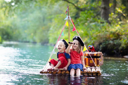 Kids dressed in pirate costumes and hats with treasure chest, spyglasses, and swords playing on wooden raft sailing in a river on hot summer day. Pirates role game for children. Water fun for family. Stock Photo