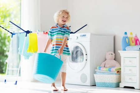 Kind in Waschküche mit Waschmaschine oder Wäschetrockner. Kind hilft bei der Hausarbeit. Moderne Haushaltsgeräte und Waschmittel im weißen sonnigen Haus. Waschen Sie gewaschene Kleidung auf dem Wäscheständer.