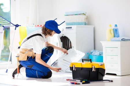 Reparaturservice für Waschmaschinen. Junger männlicher Techniker in blauer Uniform, der kaputte Waschmaschine oder Wäschetrockner untersucht und repariert. Wartung von Haushalts- und Haushaltsgeräten. Klempnerlehrling bei der Arbeit.