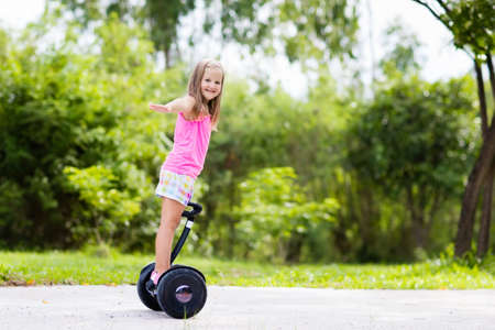 Child on hover board. Kids riding scooter in summer park. Balance board for children. Electric self balancing scooter on city street. Girl learning to ride hoverboard. Modern gadgets for school kid. Stock Photo - 103318008