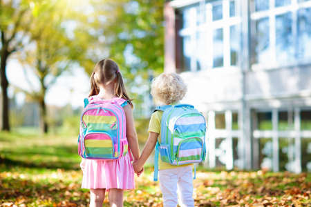 Children go back to school. Start of new school year after summer vacation. Boy and girl with backpack and books on first school day. Beginning of class. Education for kindergarten and preschool kids. Фото со стока