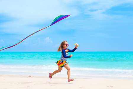 Child running with colorful kite on tropical beach. Kid flying rainbow kite. Little girl playing with toy airplane on sea shore. Family summer vacation on exotic island. Water and sand fun for kids.