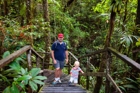 Family hiking in jungle. Father and kids on a hike in tropical rainforest. Dad and children walk in exotic forest. Travel with child. Borneo jungle and mountains. Boy and girl explore nature in Asia. 写真素材