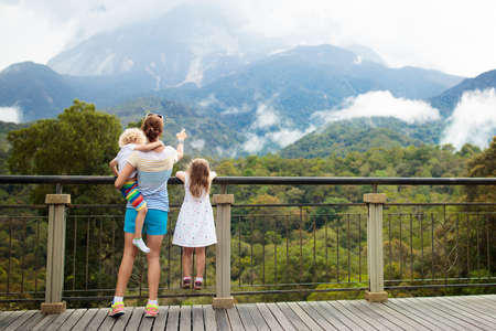 Family hiking in jungle. Mother and kids on a hike in tropical rainforest. Mom and children walk in exotic forest. Travel with child. Borneo jungle and mountains. Boy and girl explore nature in Asia. 写真素材