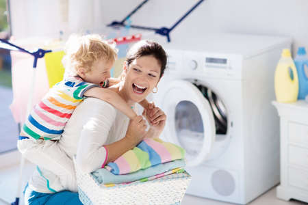 Mother and kids in the laundry room with washing machine or tumble dryer. Family chores. Modern household devices and washing detergent in white sunny home. Clean washed clothes on drying rack. Stockfoto - 103621595