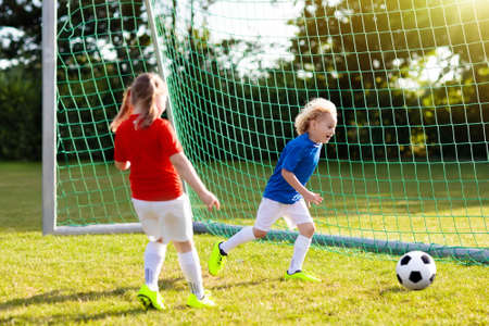 Kids play football on outdoor field. Children score a goal at soccer game. Girl and boy kicking ball. Running child in team jersey and cleats. School football club. Sports training for young player. Stockfoto