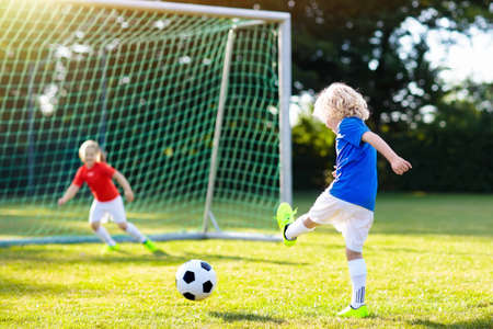 Kids play football on outdoor field. Children score a goal during soccer game. Little boy kicking ball. Running child in team jersey and cleats. School football club. Sports training for young player. 版權商用圖片 - 103621605