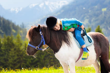 Kids riding pony in the Alps mountains. Family spring vacation on horse ranch in Austria, Tirol. Children ride horses. Kid taking care of animal. Child and pet. Little boy in saddle on pony.