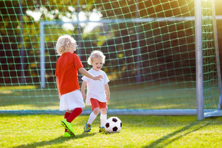 Kids play football on outdoor field. Children score a goal at soccer game. Little boy kicking ball. Running child in team jersey and cleats. School football club. Sports training for young player. Stockfoto - 103969652