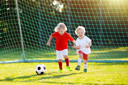 Kids play football on outdoor field. Children score a goal at soccer game. Little boy kicking ball. Running child in team jersey and cleats. School football club. Sports training for young player.
