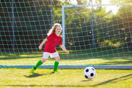 Los niños juegan al fútbol en el campo al aire libre. Fans del equipo de Portugal. Los niños marcan un gol en el partido de fútbol. Niña en camiseta portuguesa y tacos pateando la pelota. Campo de fútbol. Entrenamiento deportivo para jugador. Foto de archivo