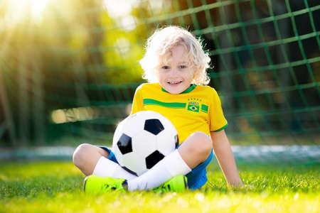 Kids play football on outdoor field. Brazil team fans. Children score a goal at soccer game. Little boy in Brazilian jersey and cleats kicking ball. Football pitch. Sports training for player. Stockfoto