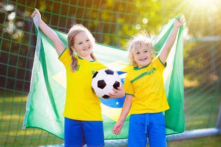 Kids play football on outdoor field. Brazil team fans with national flag. Children score a goal at soccer game. Child in Brazilian jersey and cleats kicking ball. Fan celebrating victory at pitch. Stockfoto - 103987563