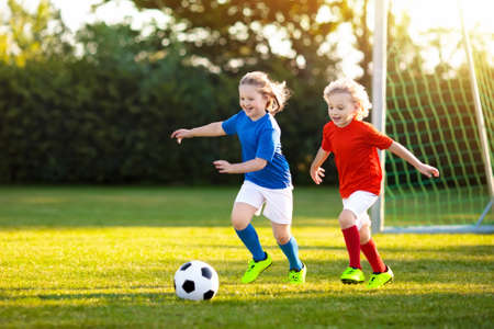 Kids play football on outdoor field. Children score a goal at soccer game. Girl and boy kicking ball. Running child in team jersey and cleats. School football club. Sports training for young player. Stock Photo