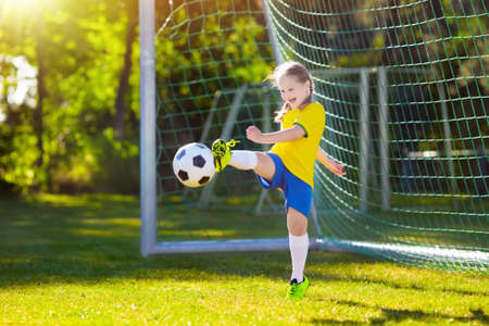 Los niños juegan al fútbol en el campo al aire libre. Fans del equipo de Brasil. Los niños marcan un gol en el partido de fútbol. Niña en jersey brasileño y tacos pateando la pelota. Campo de fútbol. Entrenamiento deportivo para jugador. Foto de archivo