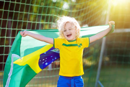 Kids play football on outdoor field. Brazil team fans with national flag. Children score a goal at soccer game. Child in Brazilian jersey and cleats kicking ball. Fan celebrating victory at pitch.