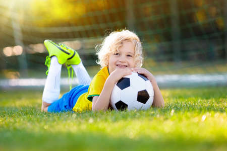Kids play football on outdoor field. Brazil team fans. Children score a goal at soccer game. Little boy in Brazilian jersey and cleats kicking ball. Football pitch. Sports training for player. Stock Photo