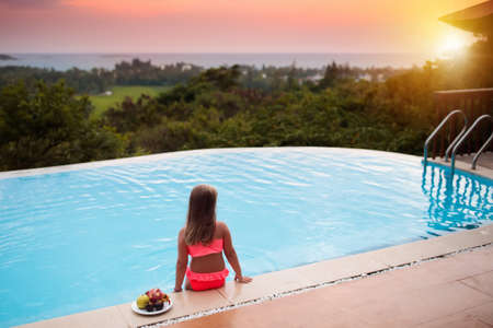 Child at swimming pool. Little girl looking at the ocean at infinity pool of tropical resort in Asia. Luxury summer vacation with kids. Family holiday.