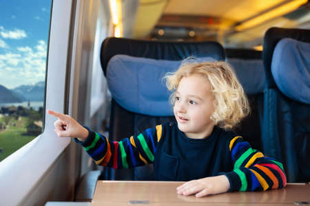 Child traveling by train. Little kid in a high speed express train on family vacation in Europe. Travel by railway. Children in railroad car. Kids in rail way wagon. Entertainment for young passenger. Archivio Fotografico