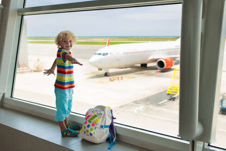 Kids at airport. Children look at airplane. Traveling and flying with child. Family at departure gate. Vacation and travel with young kid. Little boy before flight in terminal. Kids fly a plane.