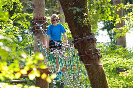 Tiener in bosavonturenpark. Tiener leeftijd jongen op hoog touwsleep. Agility- en klimcentrum voor kinderen en jonge volwassenen. Extreme buitensport. Jungle touwmanier met zipline. Stockfoto