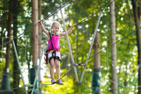 Child in forest adventure park. Kids climb on high rope trail. Agility and climbing outdoor amusement center for children. Little girl playing outdoors. School yard playground with rope way. Banque d'images - 105335121
