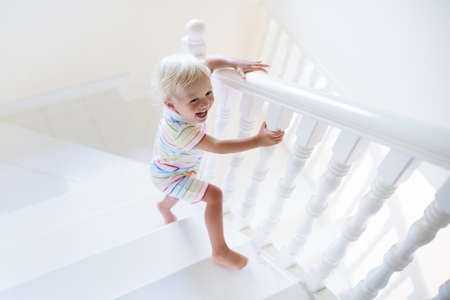 Kid walking stairs in white house. Baby boy playing in sunny staircase. Family moving into new home. Child crawling steps of modern stairway. Foyer and living room interior. Home safety for toddler.