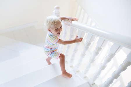 Niño caminando escaleras en la casa blanca. Baby Boy jugando en la escalera soleada. Familia que se muda a una nueva casa. Niño gateando escalones de escalera moderna. Interior de vestíbulo y sala de estar. Seguridad en el hogar para niños pequeños.