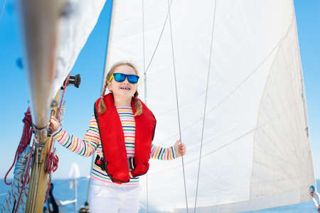 Kids sail on yacht in sea. Child sailing on boat. Little girl in safe life jackets travel on ocean ship. Children enjoy yachting cruise. Summer vacation for family. Young sailor on sailboat front deck Stok Fotoğraf - 105335379