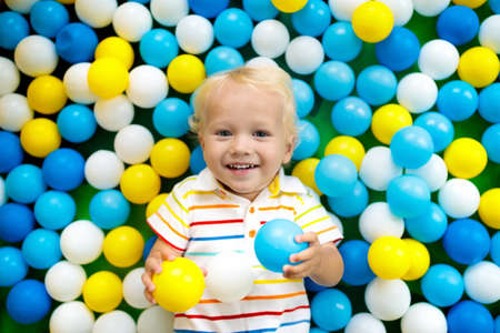 Child playing in ball pit. Colorful toys for kids. Kindergarten or preschool play room. Baby boy at day care indoor playground. Balls pool for children. Birthday party for active preschooler.
