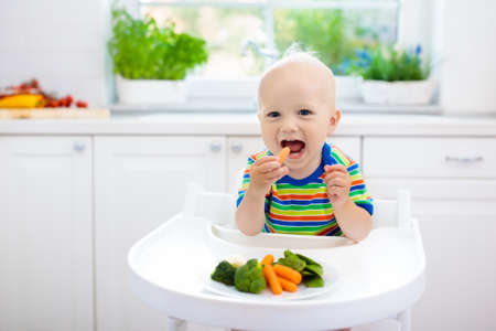 Cute baby eating vegetables in white kitchen. Infant weaning. Little boy trying solid food, organic broccoli, cauliflower, carrot and green peas. Healthy nutrition for kids. Child biting carrot. Standard-Bild