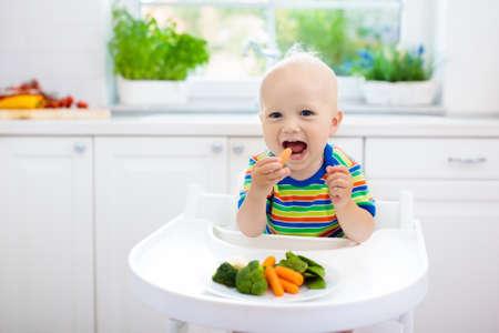 Nettes Baby, das Gemüse in der weißen Küche isst. Entwöhnung des Kindes. Kleiner Junge, der festes Essen, Bio-Brokkoli, Blumenkohl, Karotte und grüne Erbsen versucht. Gesunde Ernährung für Kinder. Kind beißt Karotte.