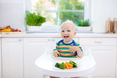 Cute baby eating vegetables in white kitchen. Infant weaning. Little boy trying solid food, organic broccoli, cauliflower, carrot and green peas. Healthy nutrition for kids. Child biting carrot. Stock Photo