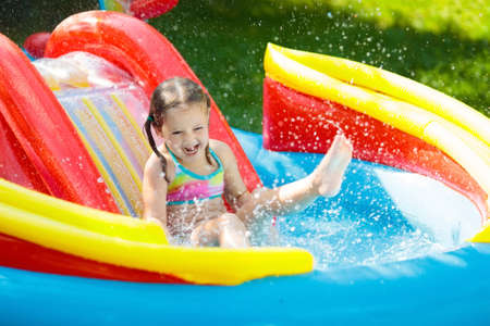 Child playing in inflatable baby pool. Kids swim, slide and splash in colorful garden play center. Happy little girl sliding and swimming with water toys on hot summer day. Family outdoor fun.