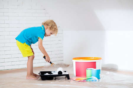 Kids painting attic wall. Home improvement and renovation. Child applying white paint on brick walls in bedroom. Renovating sky parlor with slanted walls. Family moving into new house.