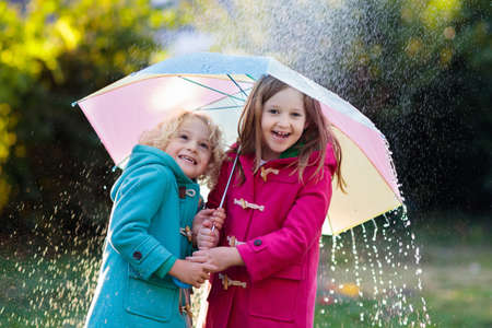 Kids with colorful umbrella playing in autumn shower rain. Little boy and girl in warm duffle coat play in a park by rainy weather. Fall outdoor fun for children. Kid catching rain drops. Foto de archivo - 107395174
