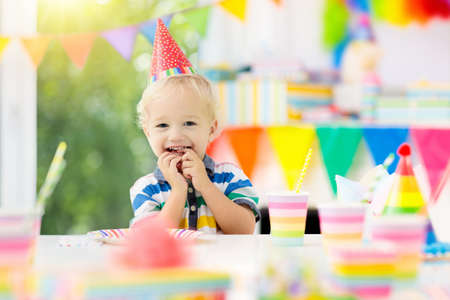 Kids birthday party. Child blowing out candles on colorful cake. Decorated home with rainbow flag banners, balloons. Farm animals theme celebration. Little boy celebrating birthday. Party food. Stok Fotoğraf - 107938645