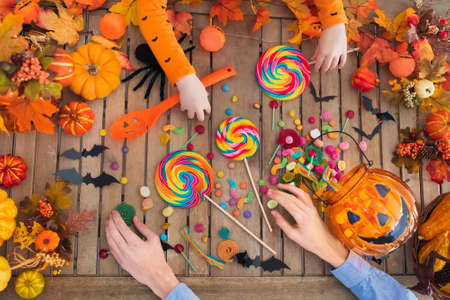Family with child carving Halloween pumpkin and eating trick or treat candy on a wooden table with autumn leaves decoration. Top view flat lay of kids hands, sweets and carved pumpkins.