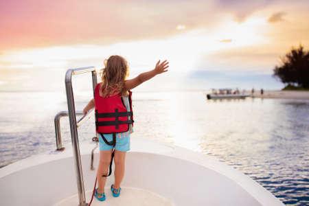 Kinder segeln auf Yacht im Meer. Kind segelt auf dem Boot. Kleines Mädchen in sicheren Schwimmwesten reisen auf Ozeanschiff. Kinder genießen Segelkreuzfahrten. Sommerferien für die Familie. Junger Seemann auf dem Vorderdeck des Segelboots Standard-Bild