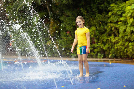 Kids play in aqua park. Children at water playground of tropical amusement park. Little girl at swimming pool. Child playing at water slide on summer vacation in Asia. Swim wear for young kid. Stock Photo - 108993784