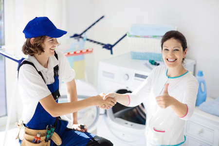 Washing machine repair service. Young technician examining and repairing tumble dryer. Woman looking at broken household appliance. Plumber with customer. Man fixing washer. Standard-Bild